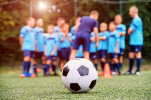 soccer-ball-blurred-youth-soccer-team-with-coach-field_85601-433